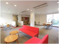 赤いソファがかわいいラウンジ。 ラウンジには居心地のいい図書コーナーも!